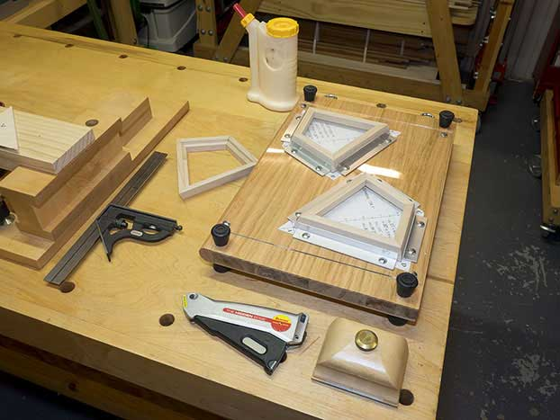 A view of two deltoid-shaped frame pieces drying in the gluing jig