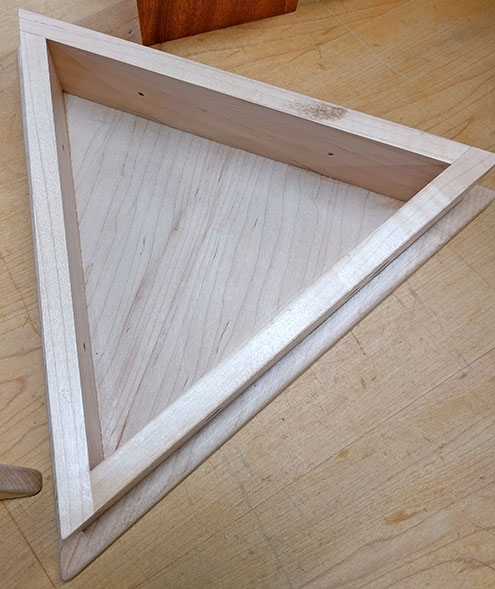 The simple triangular maple box that the triangular shoulder will sit on top of