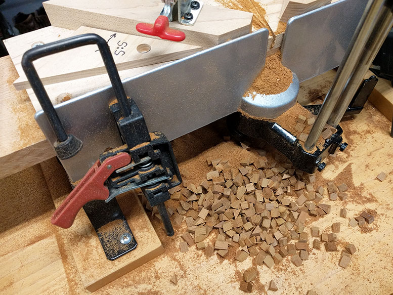 The pile of mahogany cutoffs and sawdust behind the miter saw