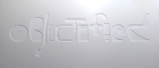 A still from the DVD Objectified, showing the title etched in white plastic